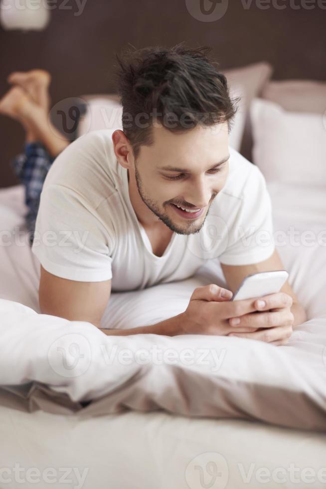 fröhlicher Mann SMS mit jemandem lustig foto