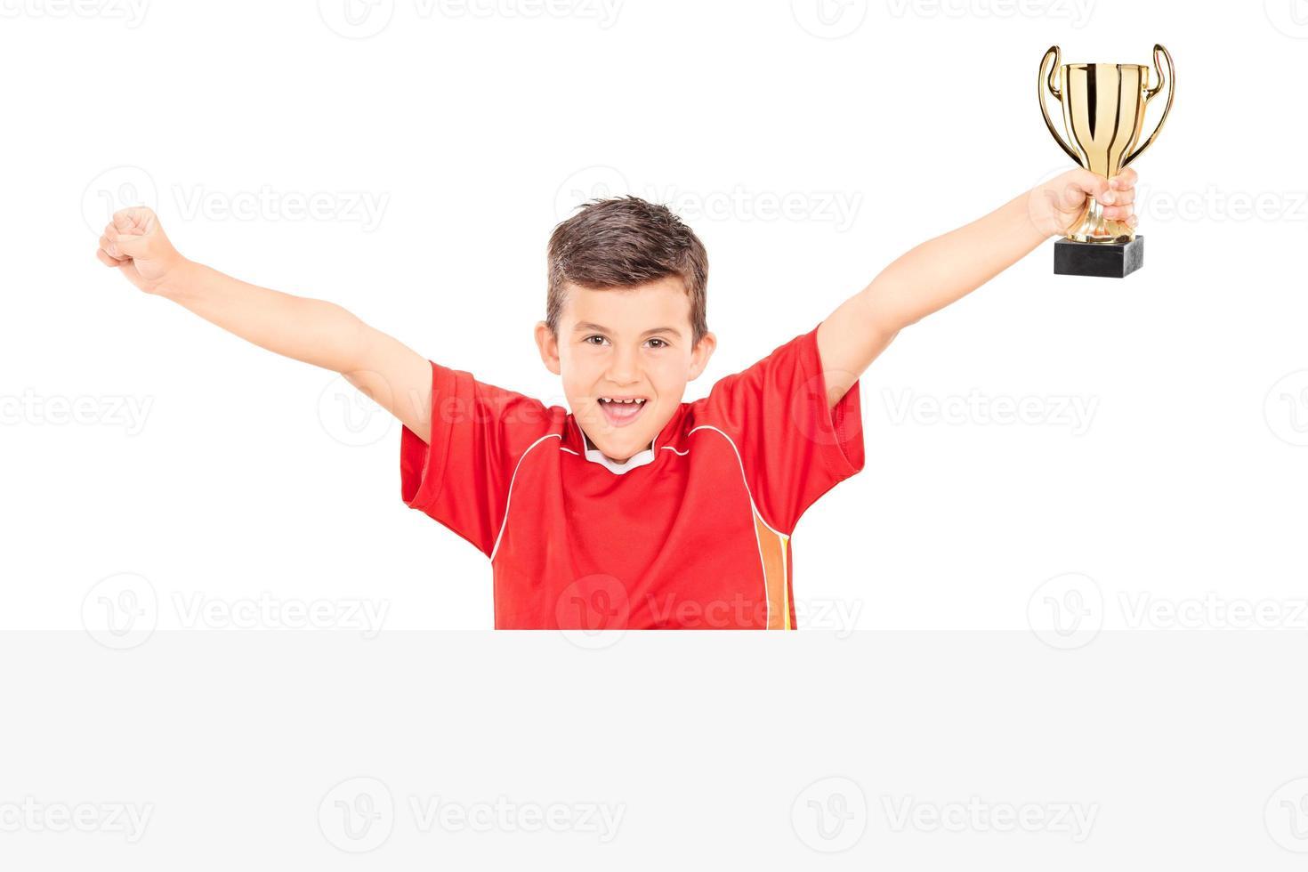 fröhlicher Junior, der eine Trophäe hinter einer Tafel hält foto