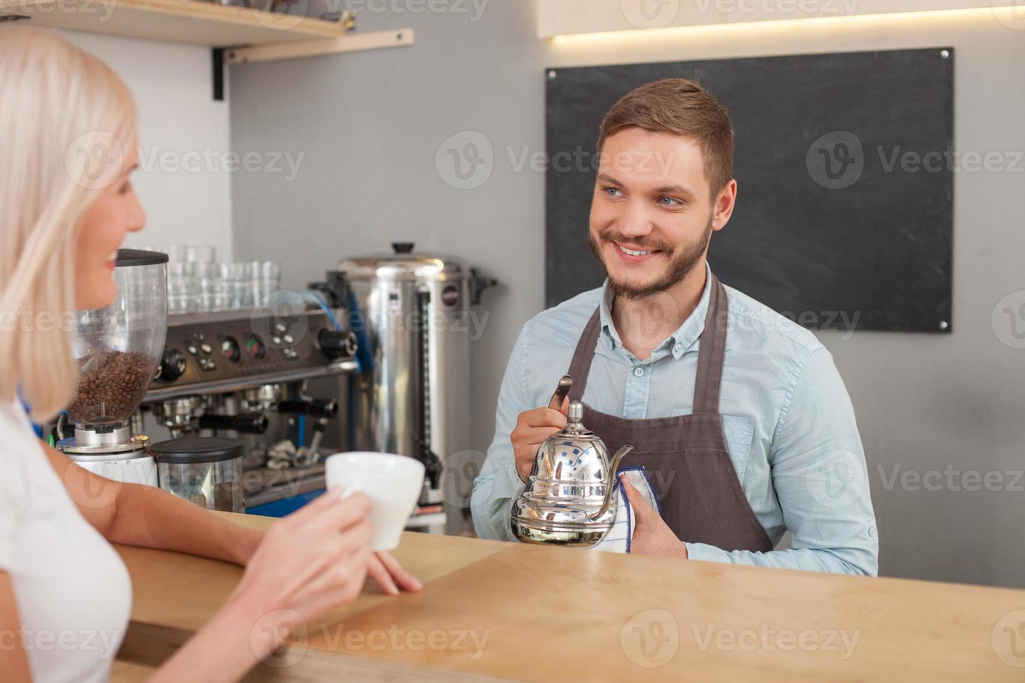 fröhlicher männlicher Besitzer der Cafeteria dient Kunden foto