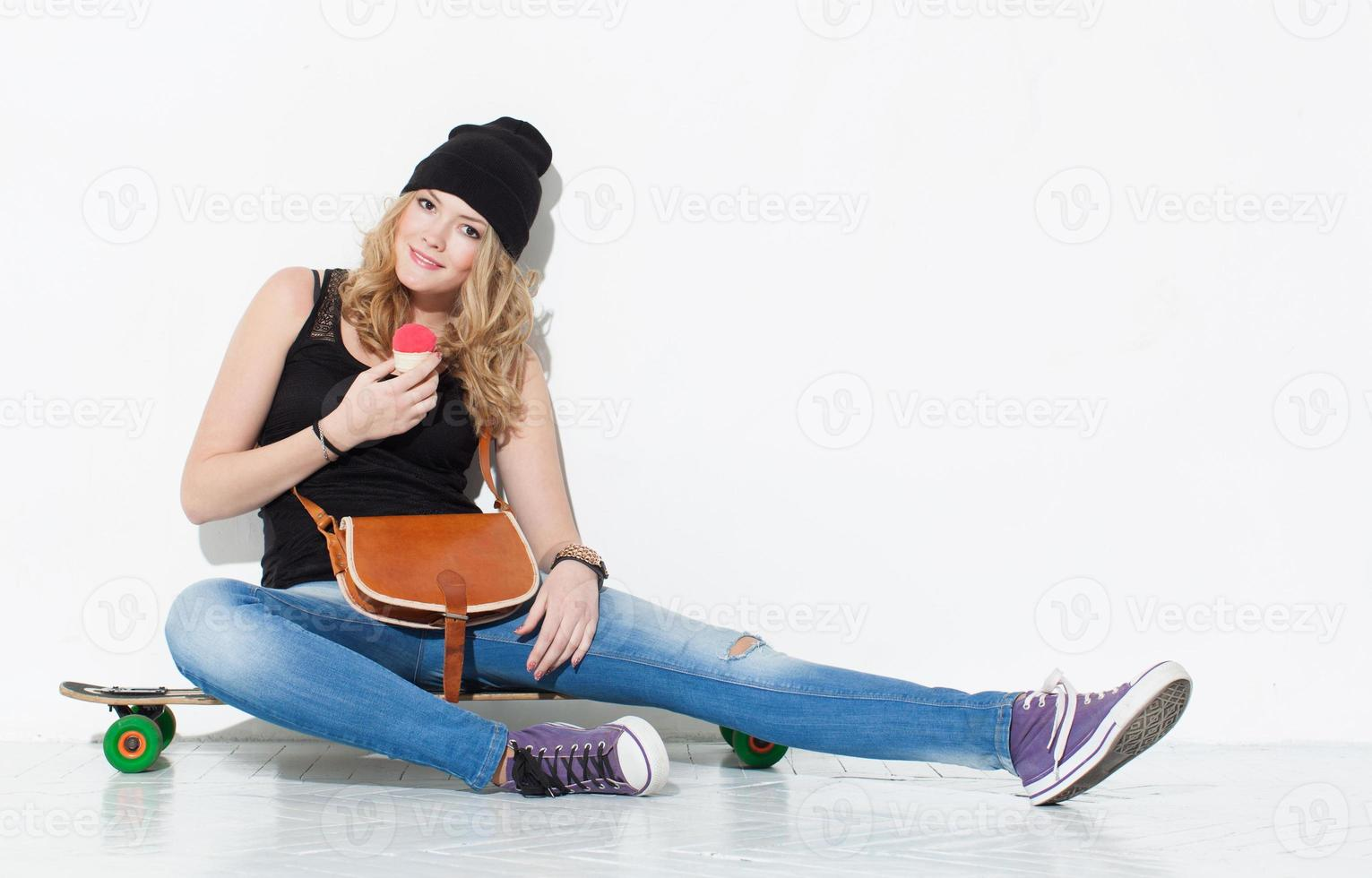 junges schönes fröhliches Mode-Mädchen in Jeans, Turnschuhen foto