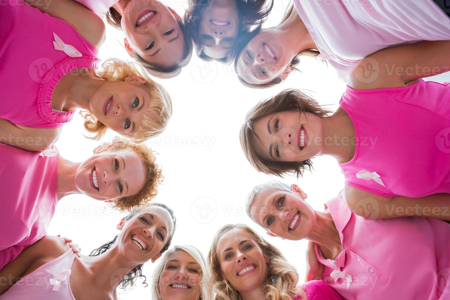 fröhliche Frauen im Kreis, die Rosa für Brustkrebs tragen foto
