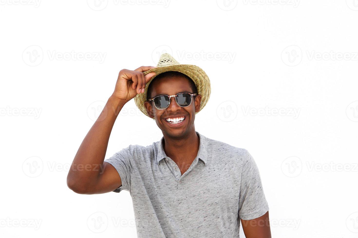 fröhlicher Afroamerikaner, der mit Hut und Sonnenbrille lächelt foto