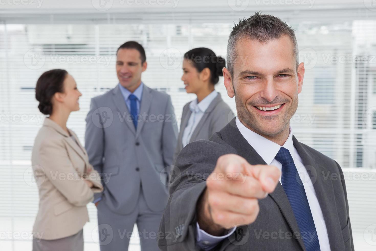fröhlicher Geschäftsmann, der mit Kollegen auf backgr Kamera zeigt foto