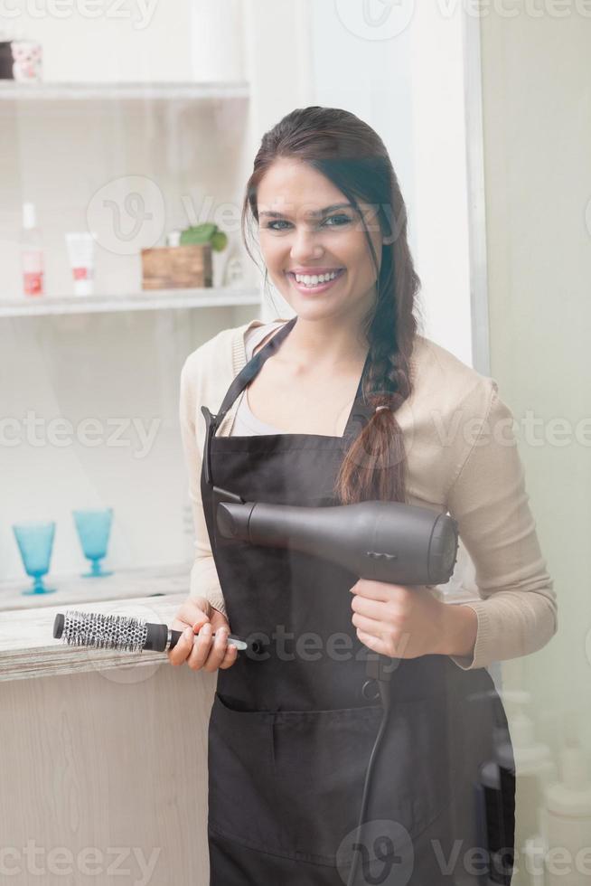 fröhlicher Friseur, der Kamera betrachtet foto