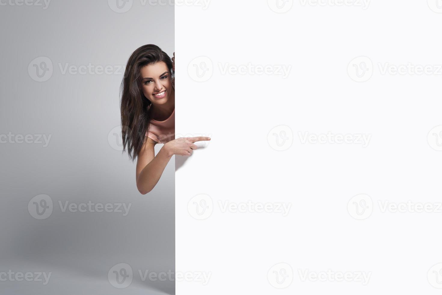 glückliche Frau, die auf Kopienraum auf Whiteboard zeigt foto