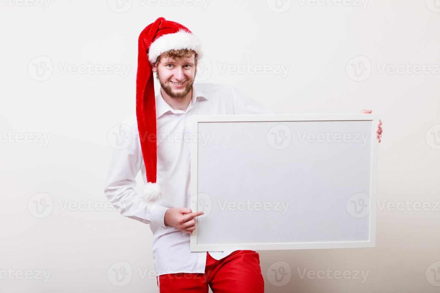 Mann in Weihnachtsmütze mit leerem Banner. Speicherplatz kopieren. foto