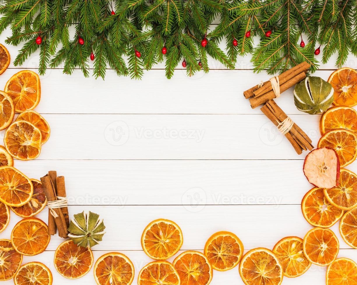 Weihnachtsbaum, getrocknete Orangen, Zimt, weißer hölzerner Hintergrund, Kopienraum. foto