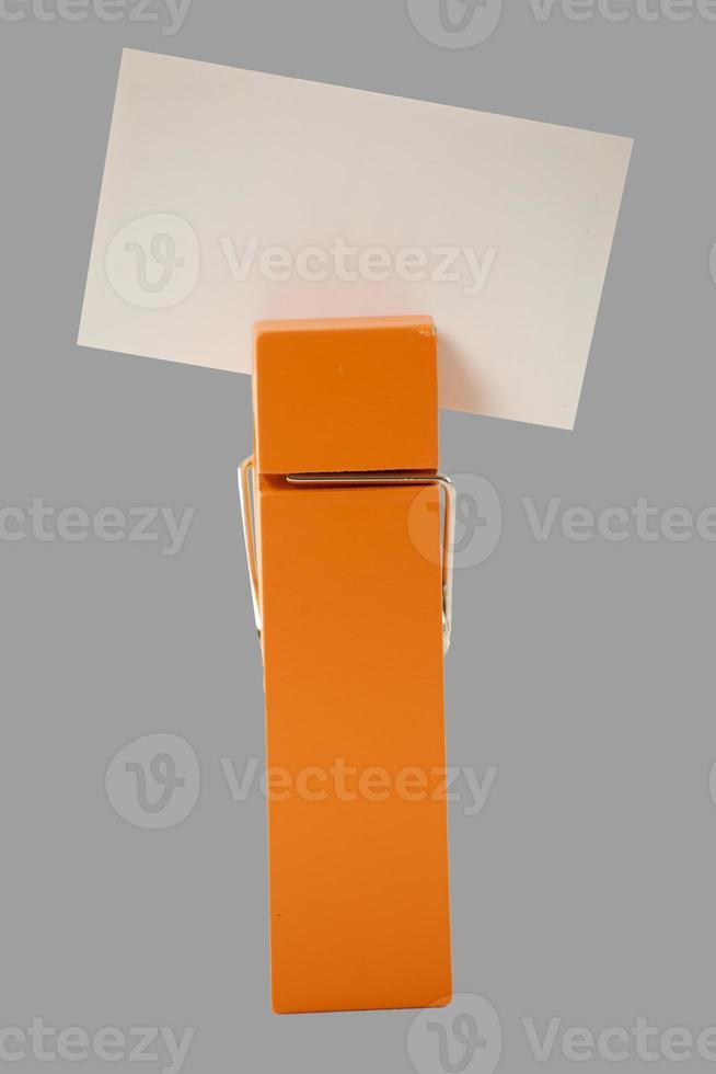 orange Wäscheklammer, die eine Notiz mit grauem Hintergrund hält foto