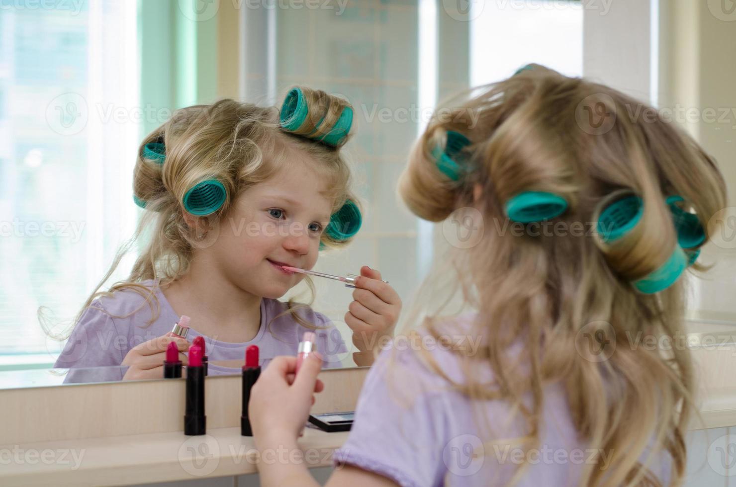 blondes Mädchen mit Lippenstift und Lockenwicklern foto