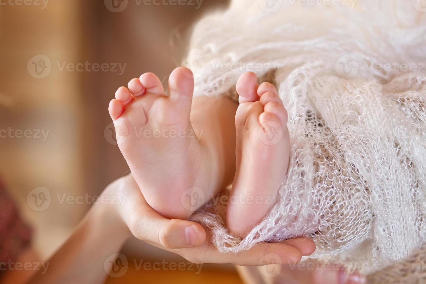 Babyfüße in Mutterhänden. Mutter und ihr Kind. foto
