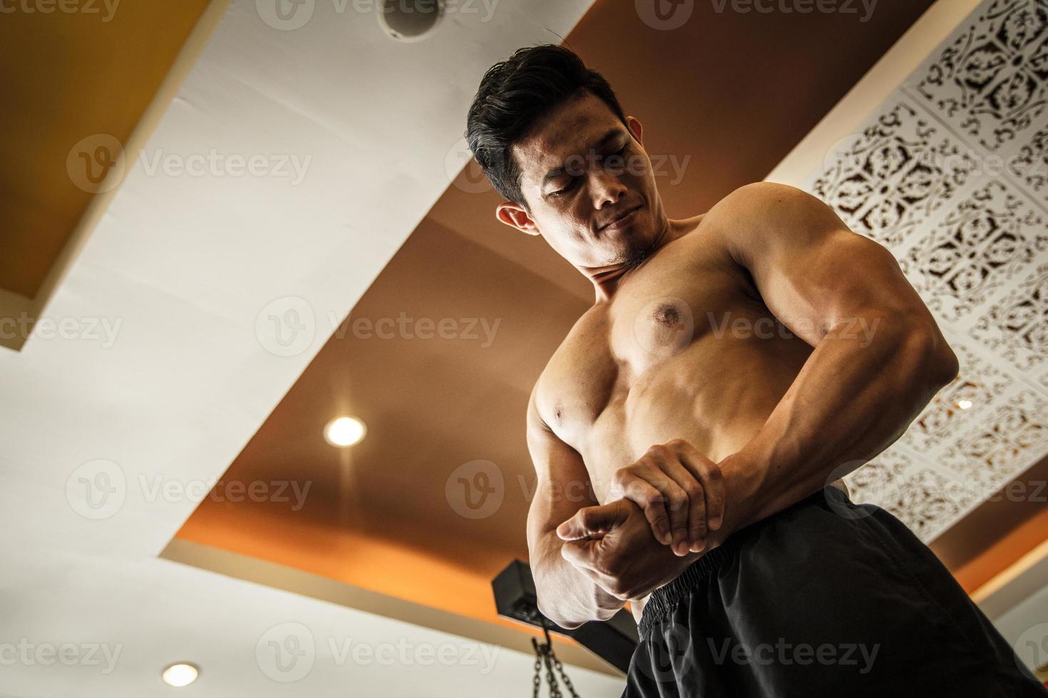 Bodybuilder schaut seinen Muskel foto