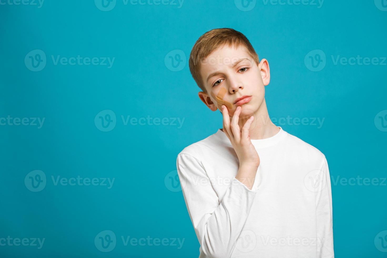 unglücklicher Junge mit Heftpflaster auf der Wange foto