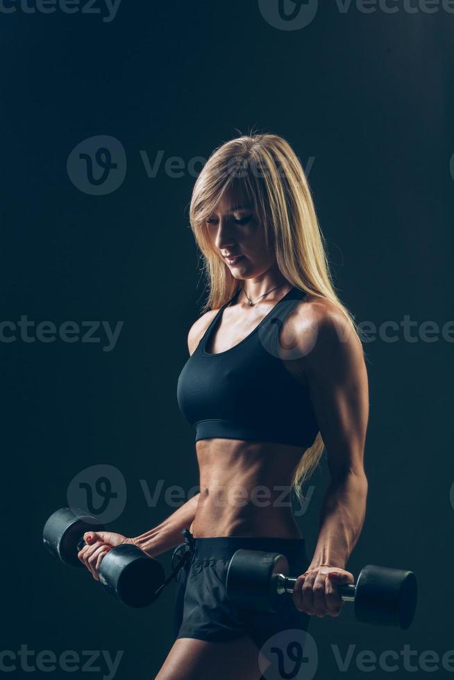 sportliche Frau mit Hanteln auf einem dunklen Hintergrund foto