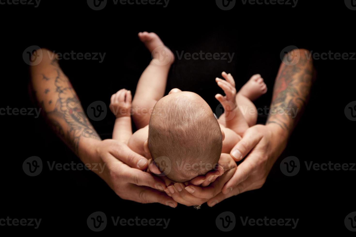 Hände von Vater und Mutter halten Neugeborenes auf Schwarz foto