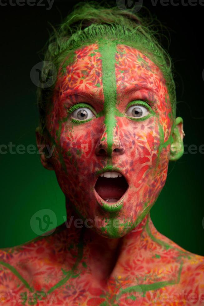 emotionale Frau mit roten Mehrfachlinien und grünen Haaren foto