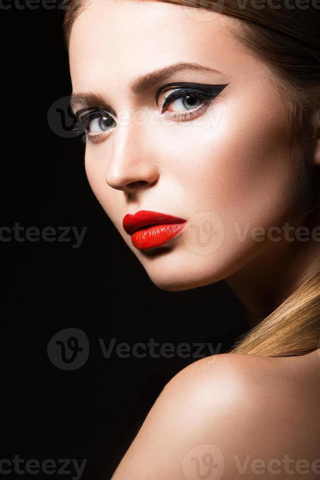 schönes Mädchen mit ungewöhnlichen schwarzen Pfeilen und roten Lippen. foto