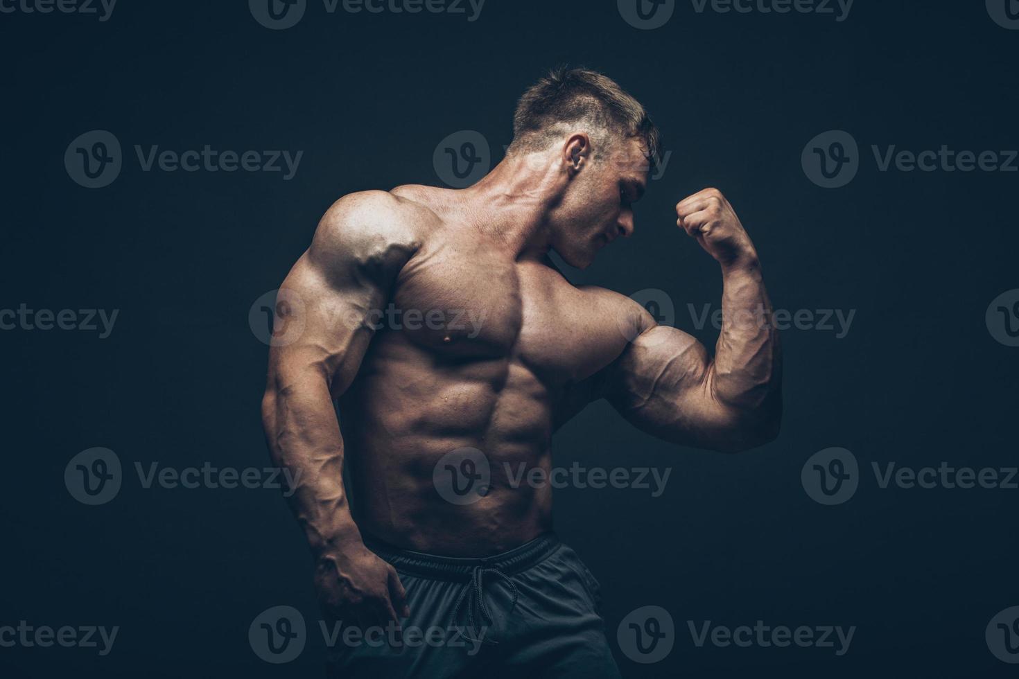 schöner muskulöser Bodybuilder, der über schwarzem Hintergrund aufwirft foto