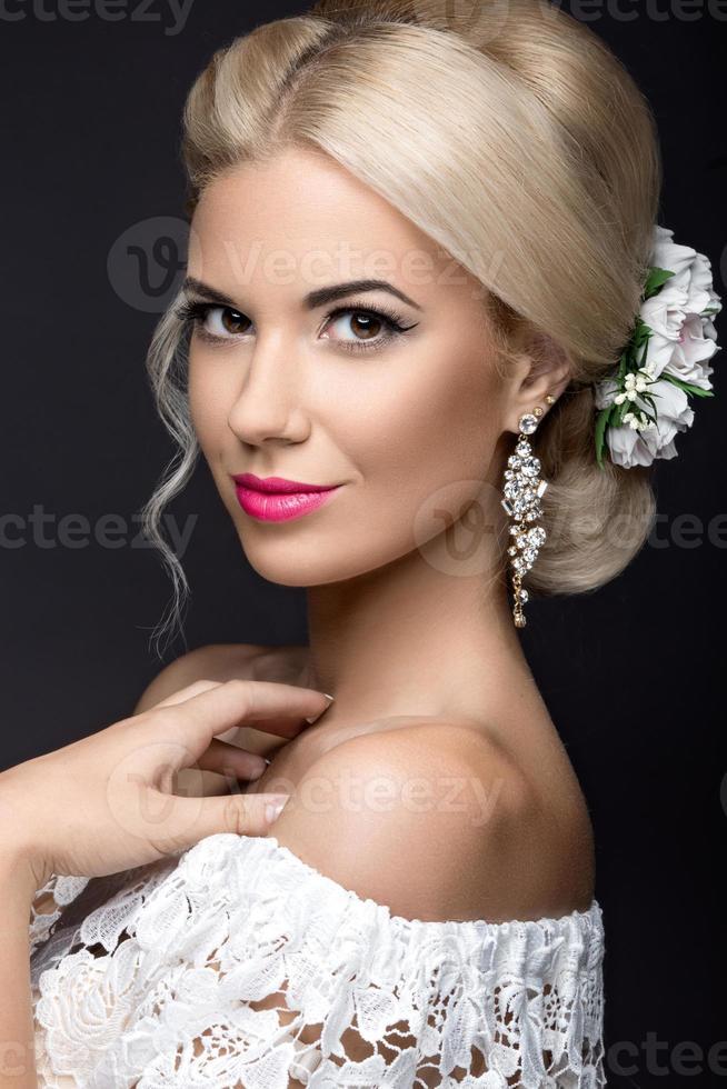 schöne blonde Frau im Bild der Braut mit Blumen foto