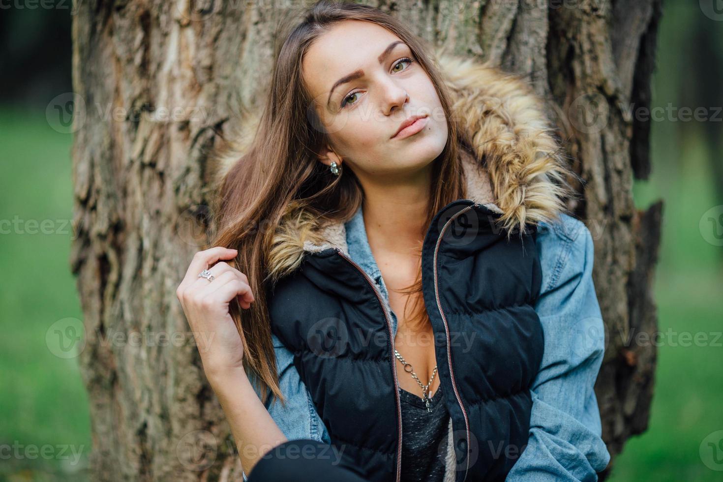 junges hübsches Mädchen, das nahe dem Baum steht. foto