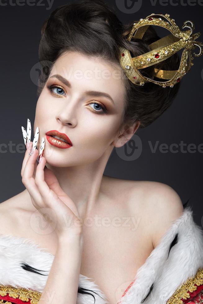 schönes Mädchen im Bild der Königin mit langen Nägeln foto
