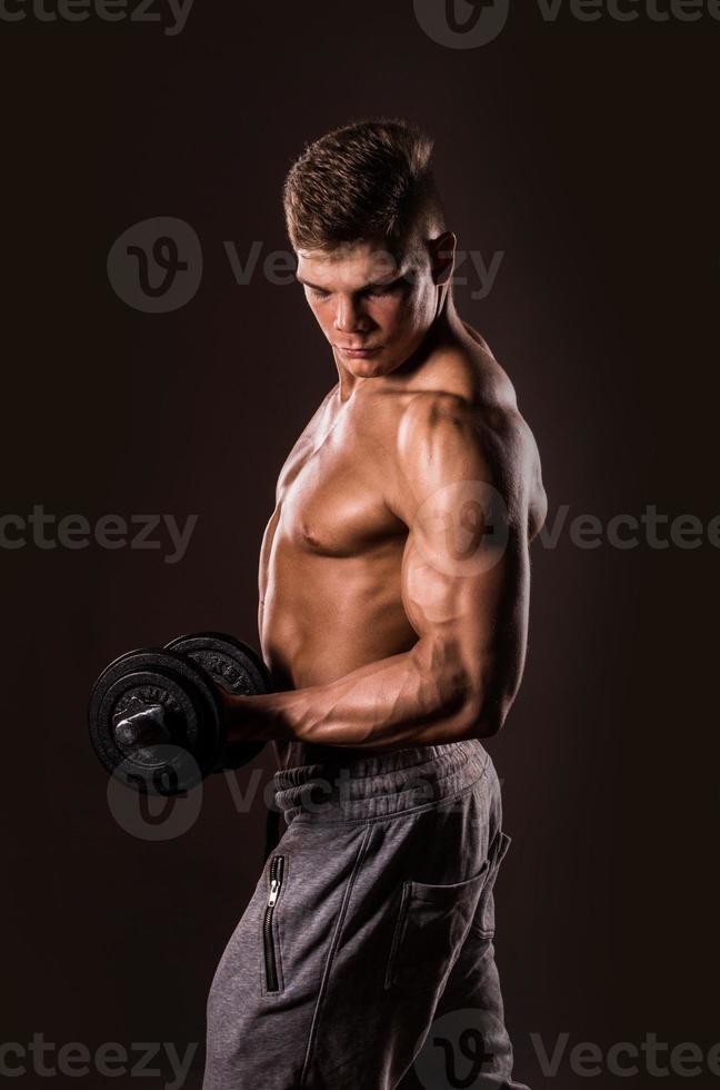 Bodybuilder Mann hält Gewichte foto