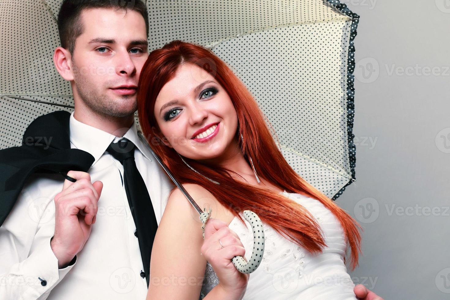 glücklicher Brautpaar-Bräutigam auf grauem Hintergrund foto