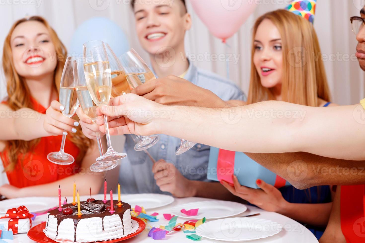 junge Leute, die einen Geburtstag feiern, der am Tisch sitzt foto