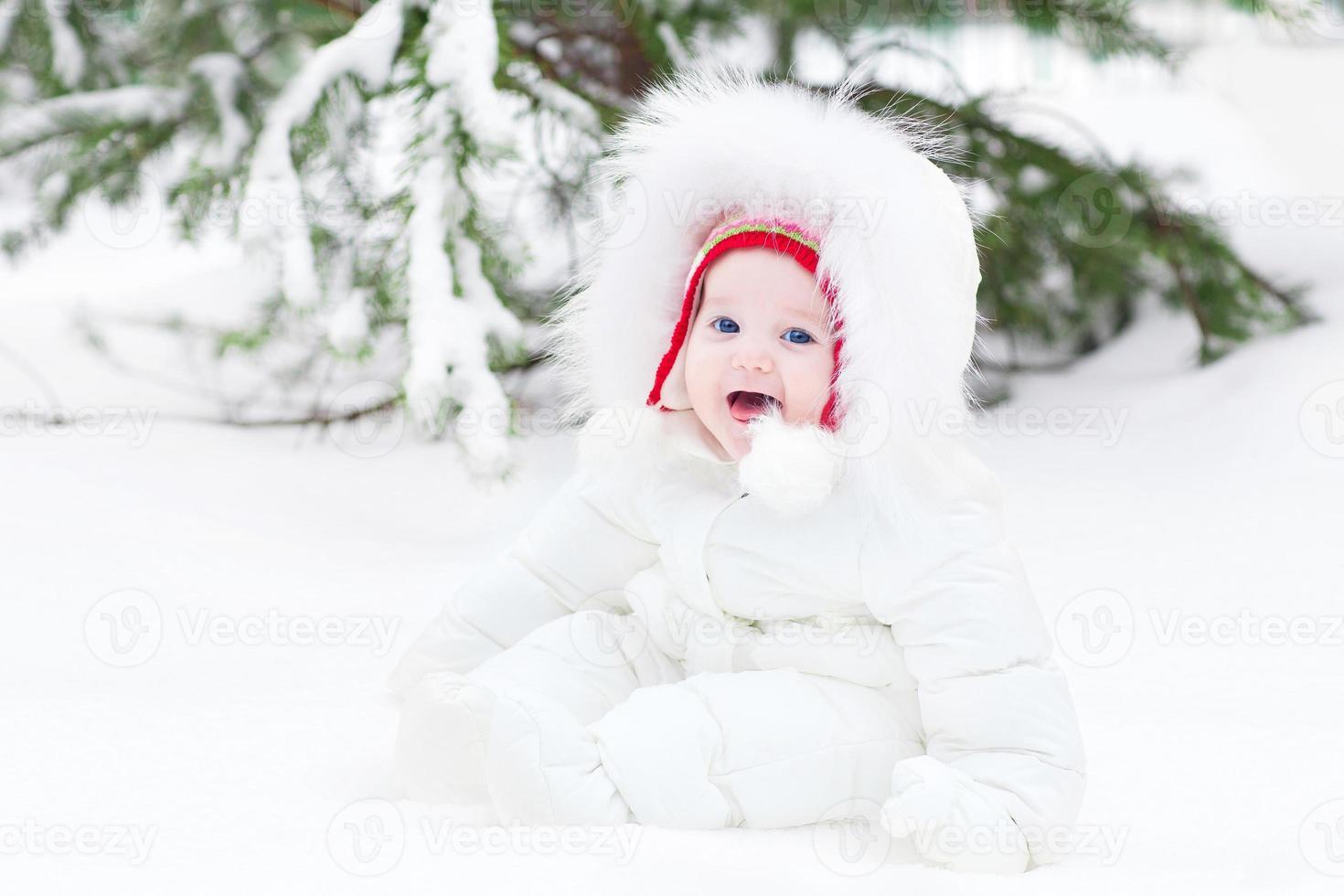 entzückendes lachendes Baby, das im Schnee unter Weihnachtsbaum sitzt foto