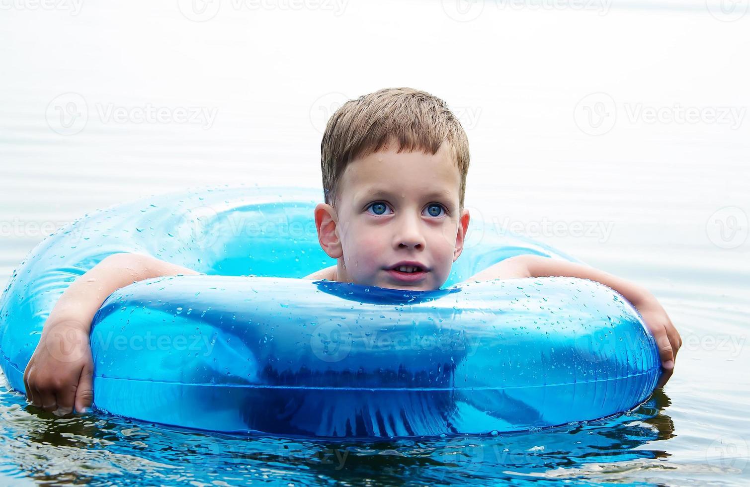 Junge, der sich auf einem Wasserschlauch entspannt foto