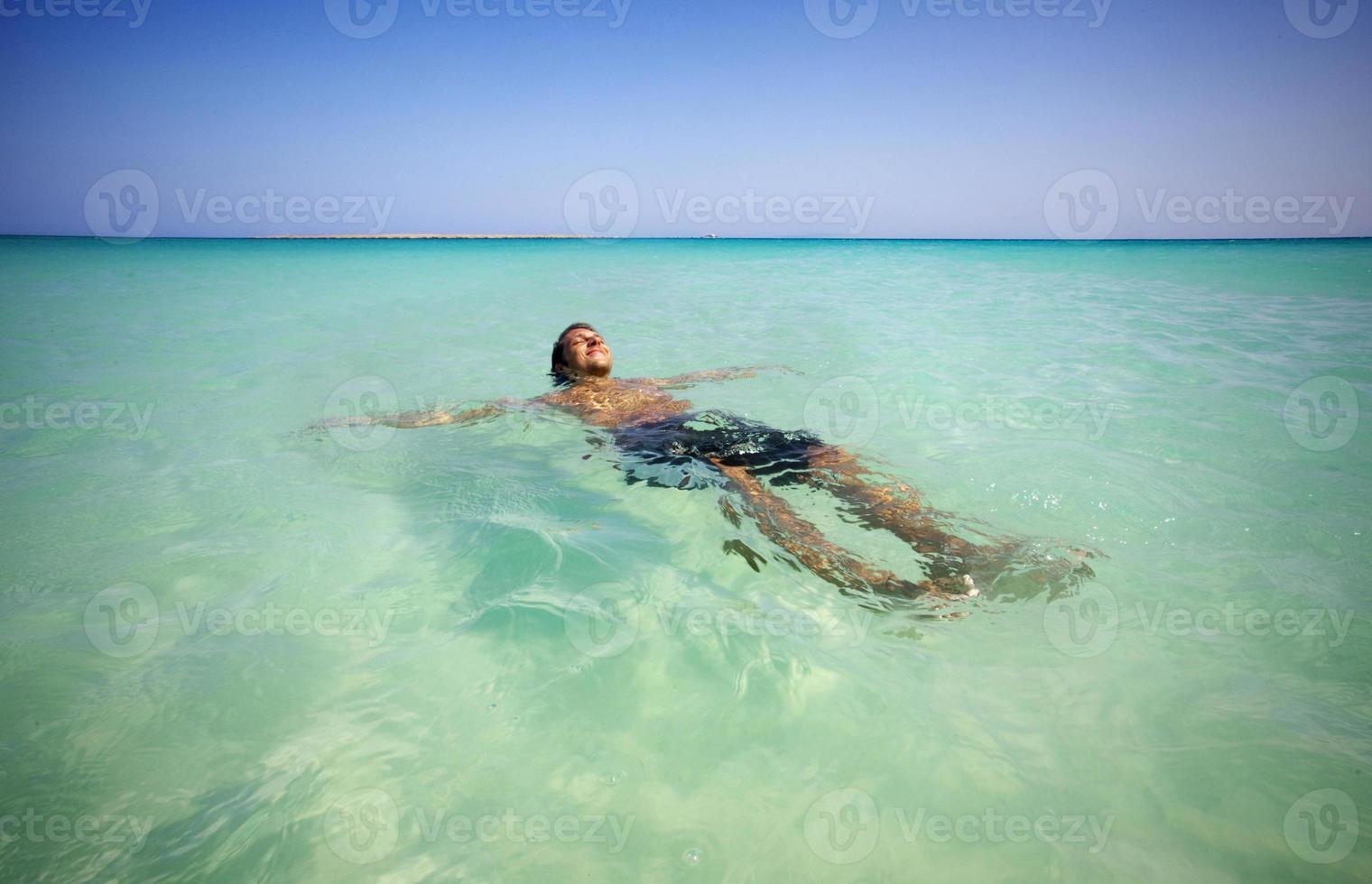 Der Mann entspannt sich im Meer foto