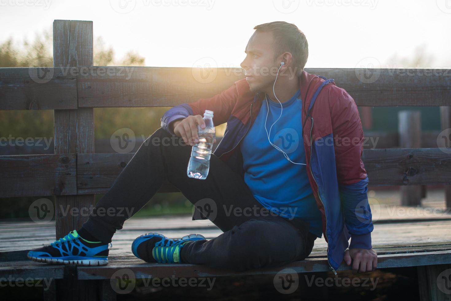 Müde Läufer sitzen, entspannen und Musik hören Telefon auf foto