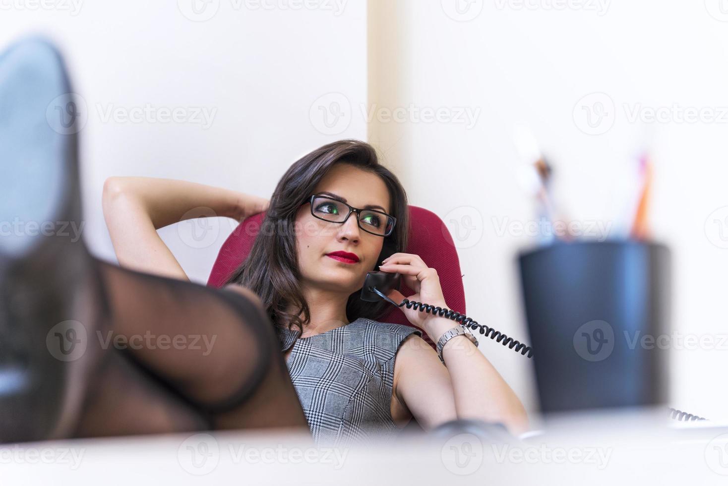Entspannen Sie Geschäftsfrau, die am Telefon spricht und ihren Laptop benutzt foto