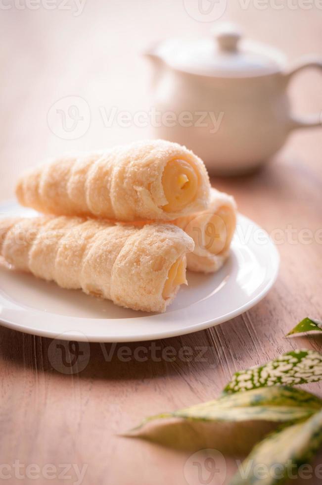 Cremegefüllte Gebäckrolle auf dem Holzbrett, entspannende Teezeit foto