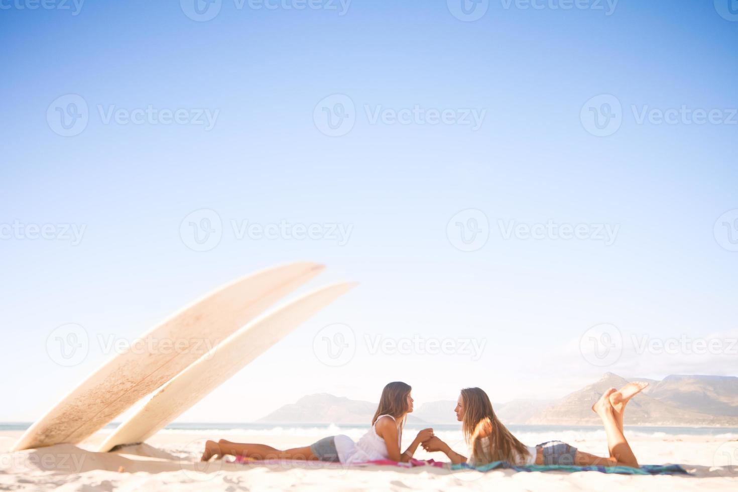 beste Freunde, die sich an den Händen halten und im Schatten entspannen foto