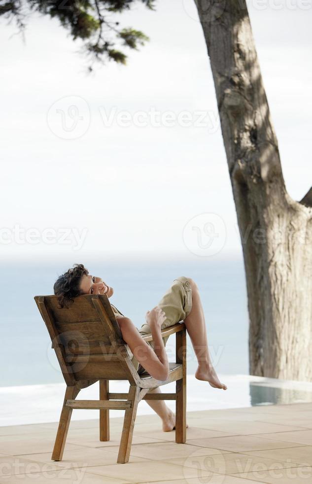 Porträt der Frau, die auf Liegestuhl durch Infinity-Pool entspannt foto