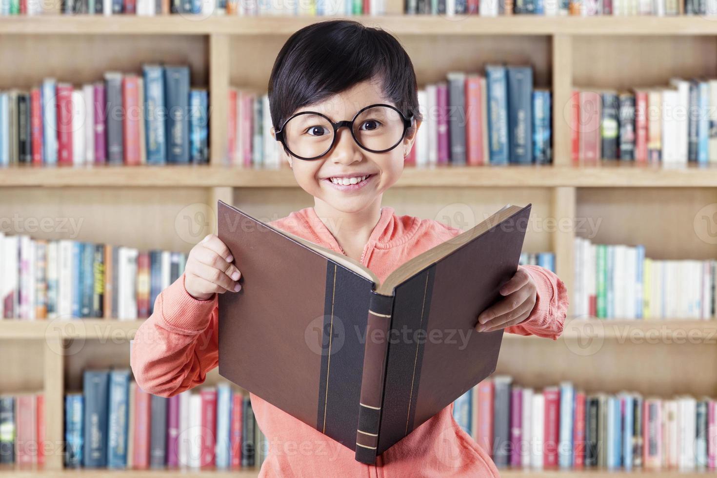 Mädchen, das in der Bibliothek beim Lesen des Lehrbuchs steht foto