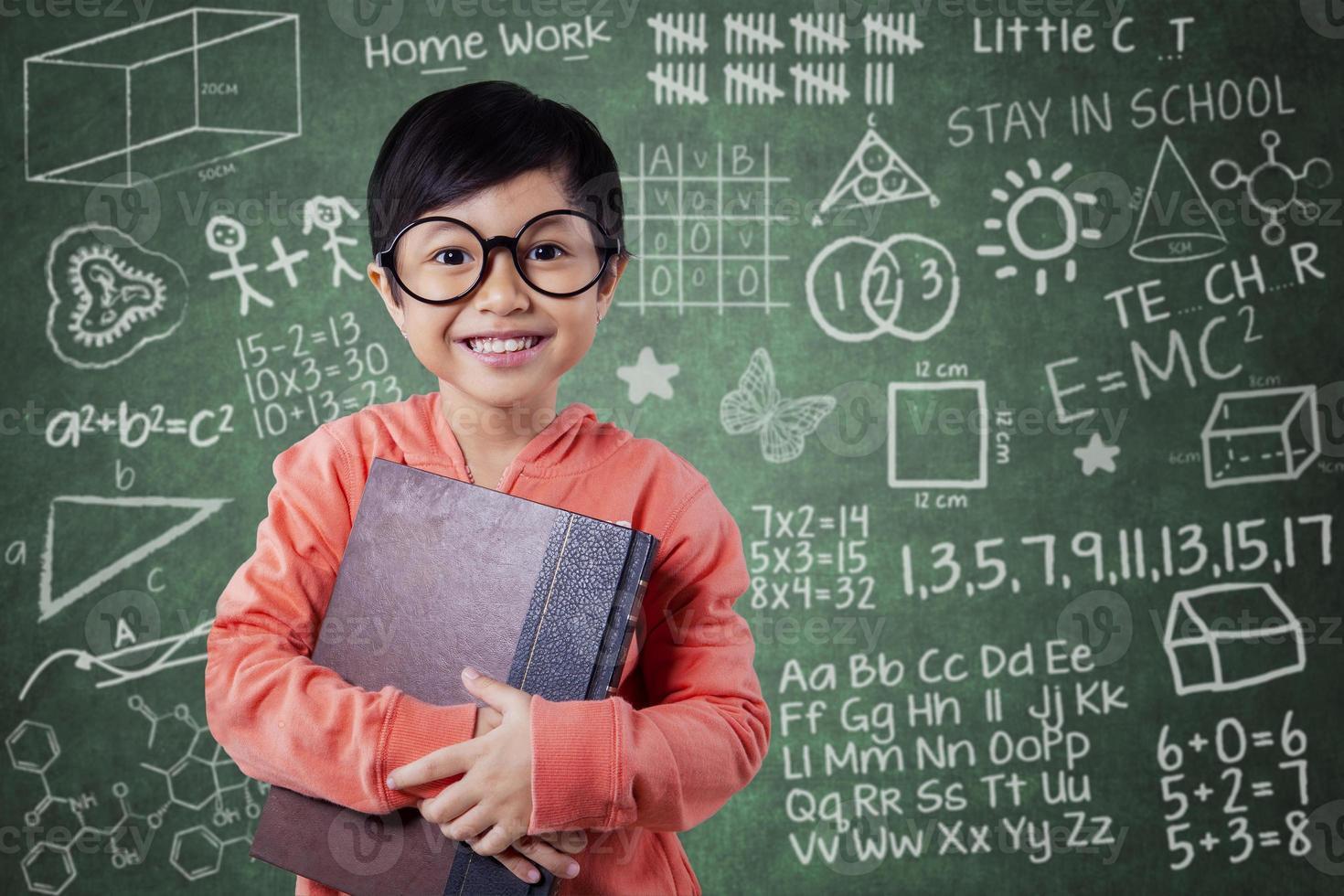 süßes kleines Mädchen hält Lehrbuch in der Klasse foto