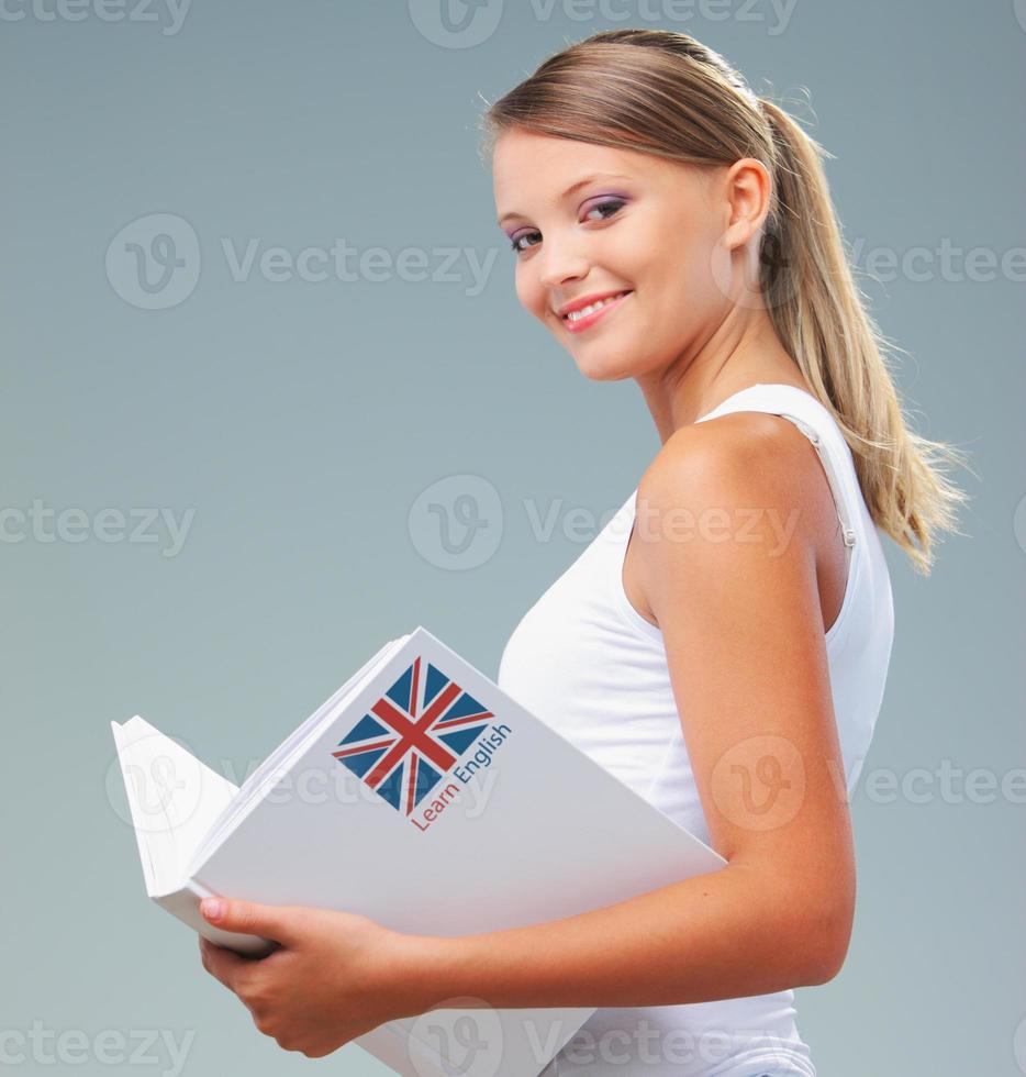 eine Studentin mit einem englischen Lehrbuch foto