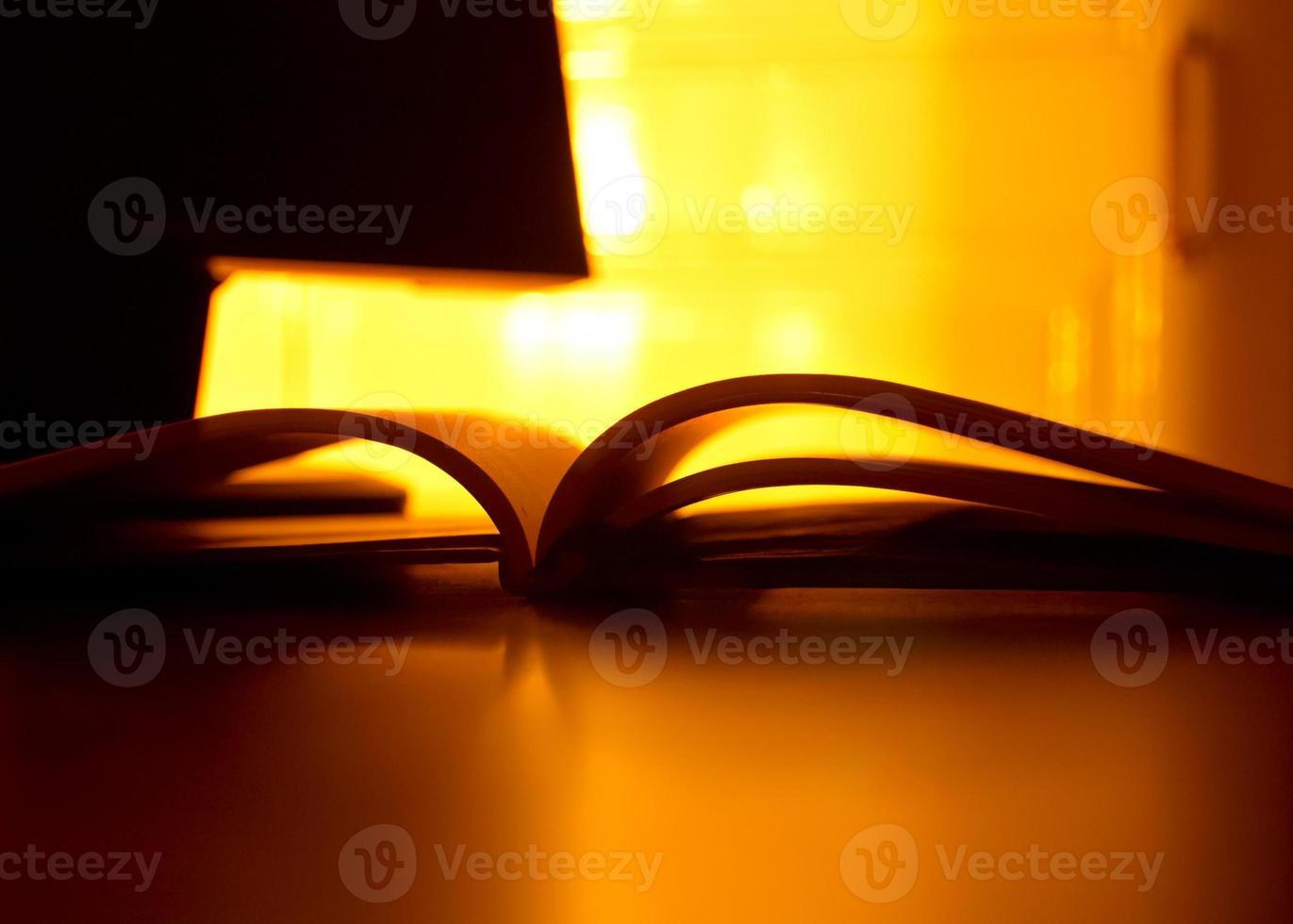 Langzeitbelichtung des offenen Buches im reflektierten Kerzenlicht foto