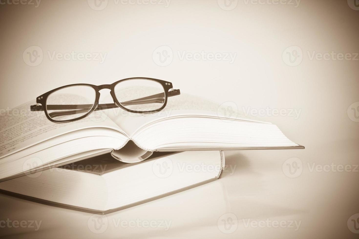 schwarze Brille auf geöffnetem Buch foto