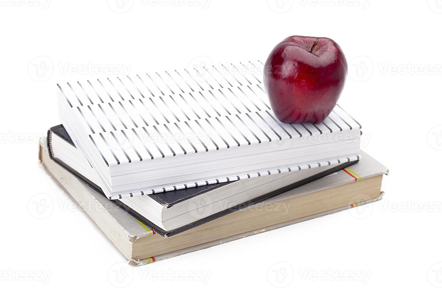 Stapel Bücher mit einem Apfel oben drauf foto
