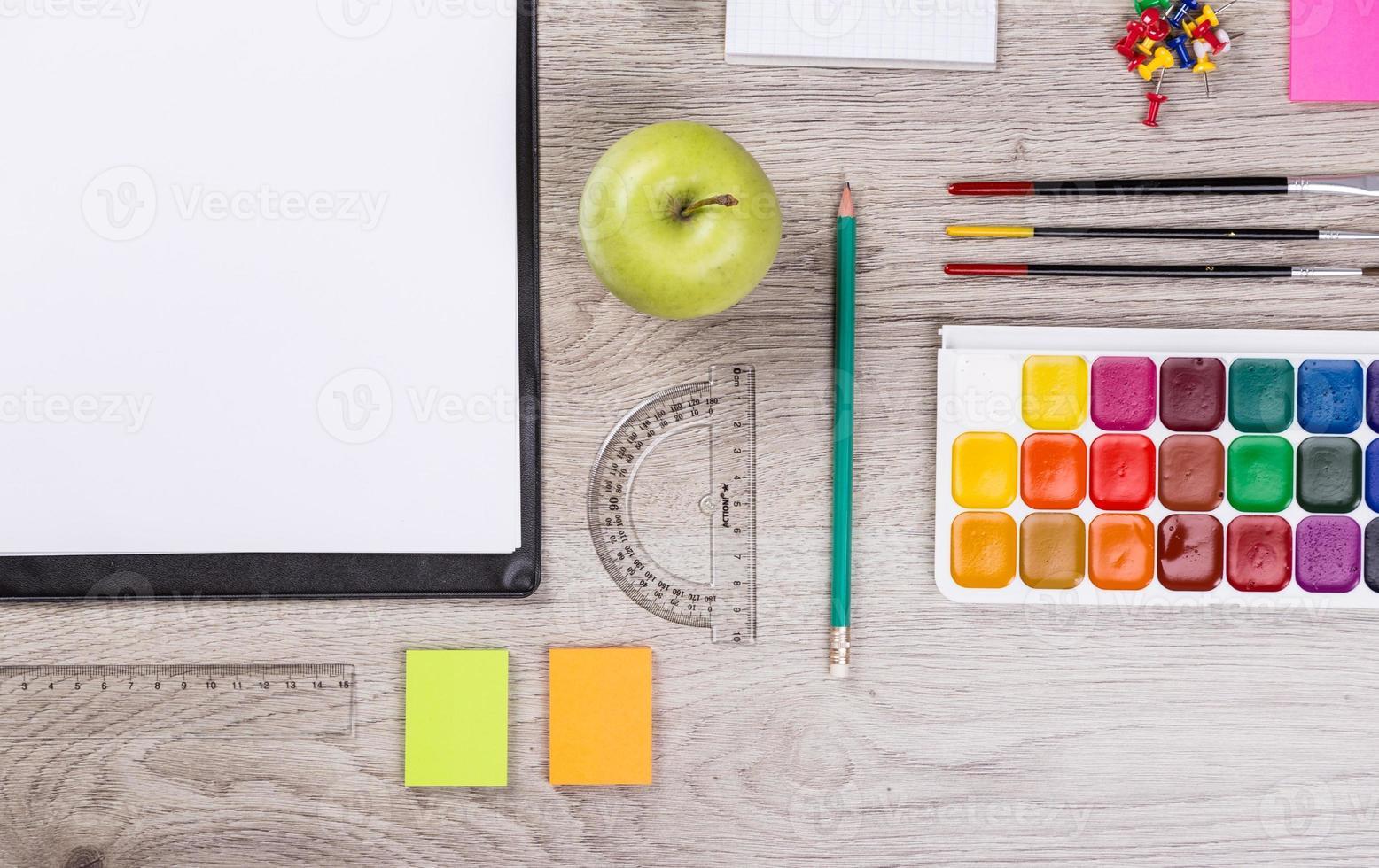 Papier, Bleistifte, Pinsel, grüner Apfel auf Holztisch foto