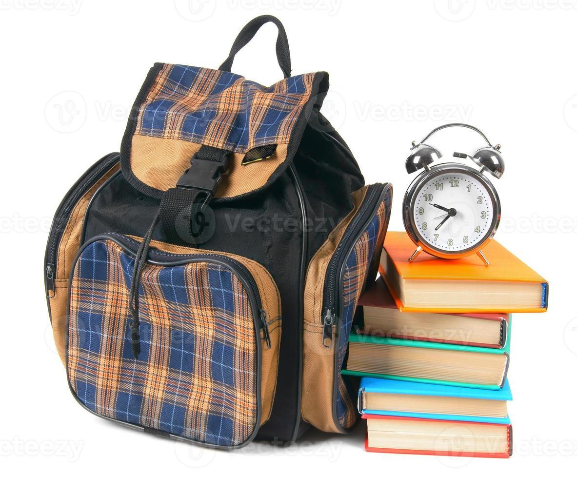 Schulrucksack, Bücher und Wecker. foto