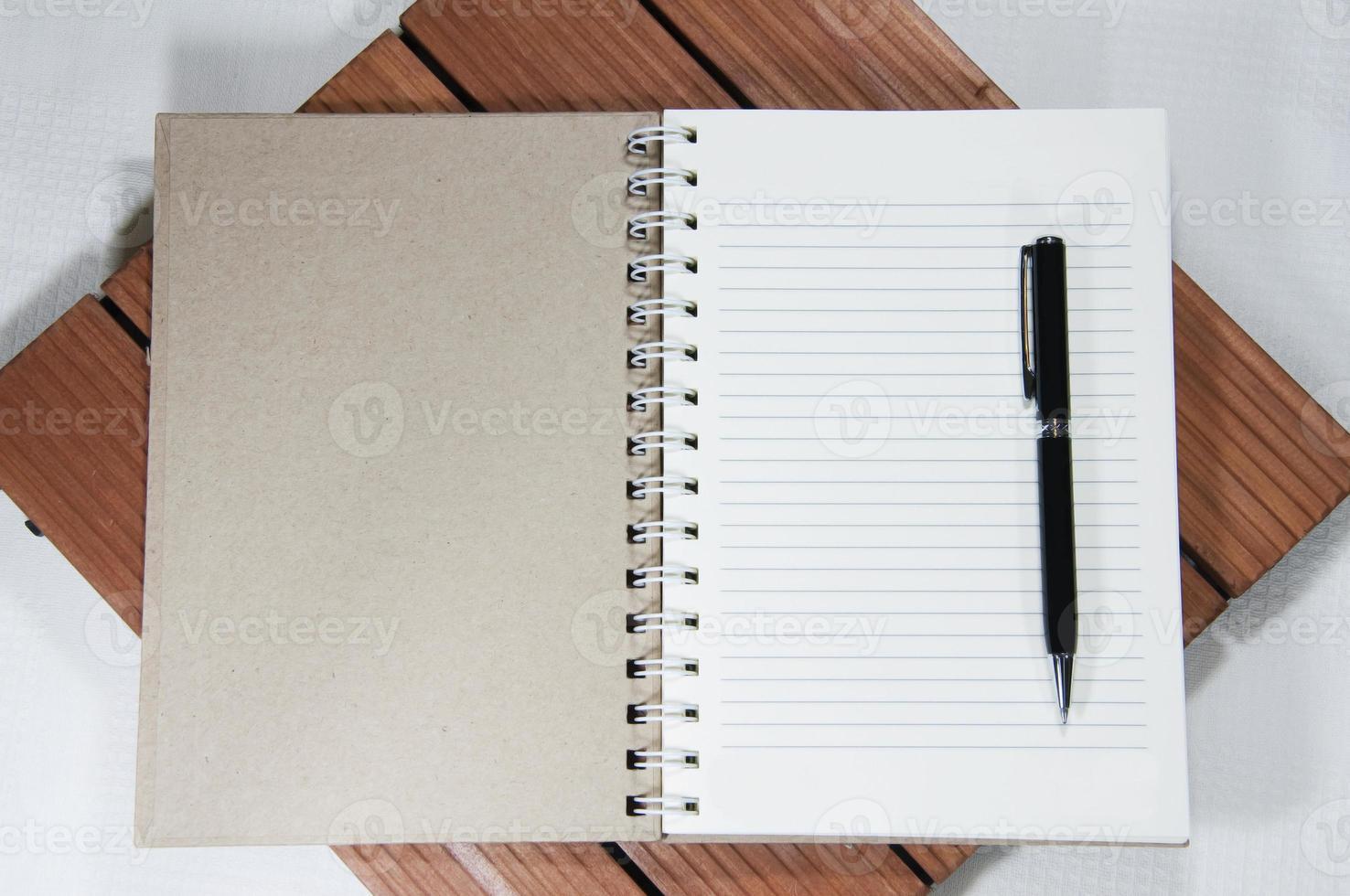 leeres weißes Notizbuch und Stift auf dem Holz foto