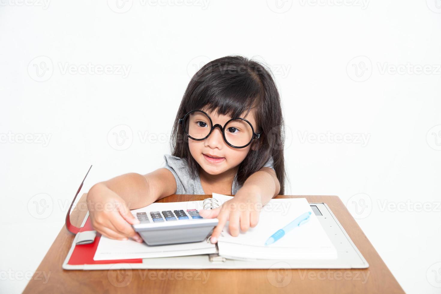 kleine asiatische Studentin mit Notizbuch und Taschenrechner isolieren foto