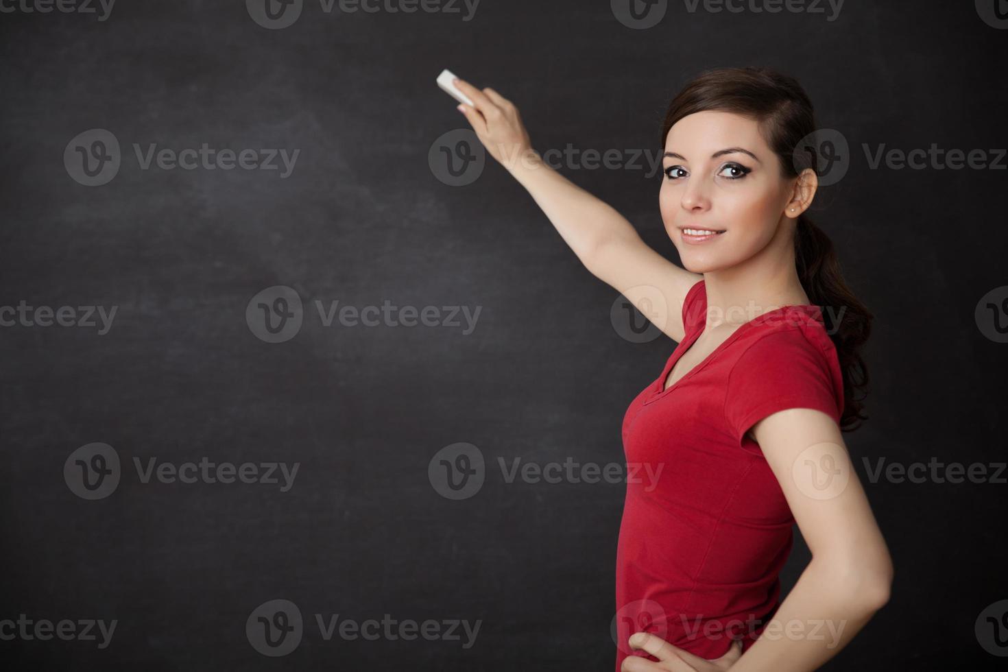 Frau, die an Tafel schreibt foto