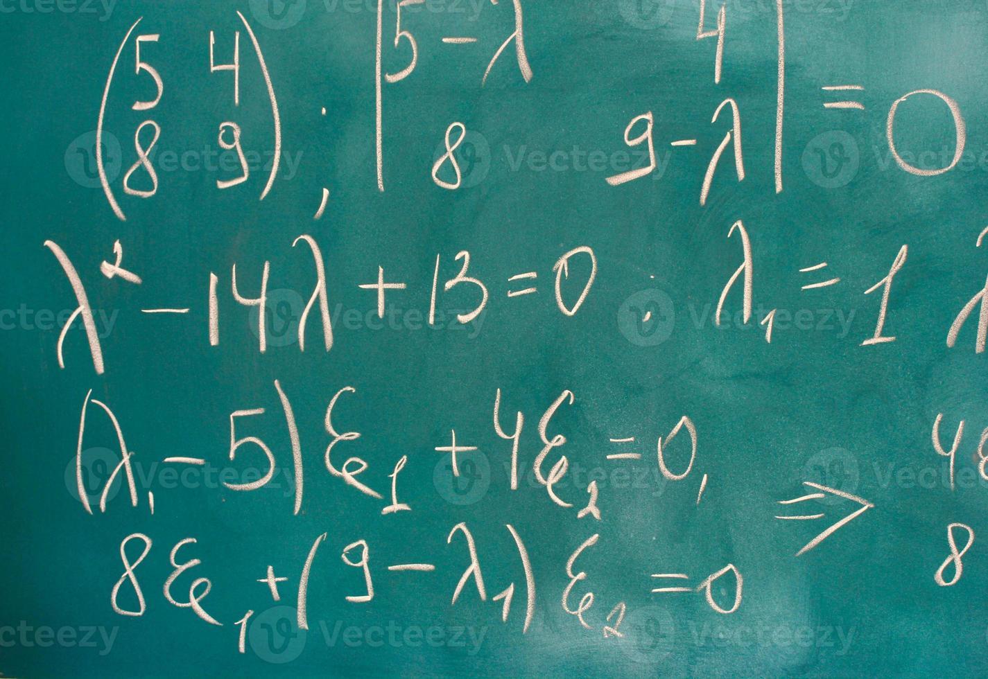 Formeln auf grüner Tafel geschrieben foto