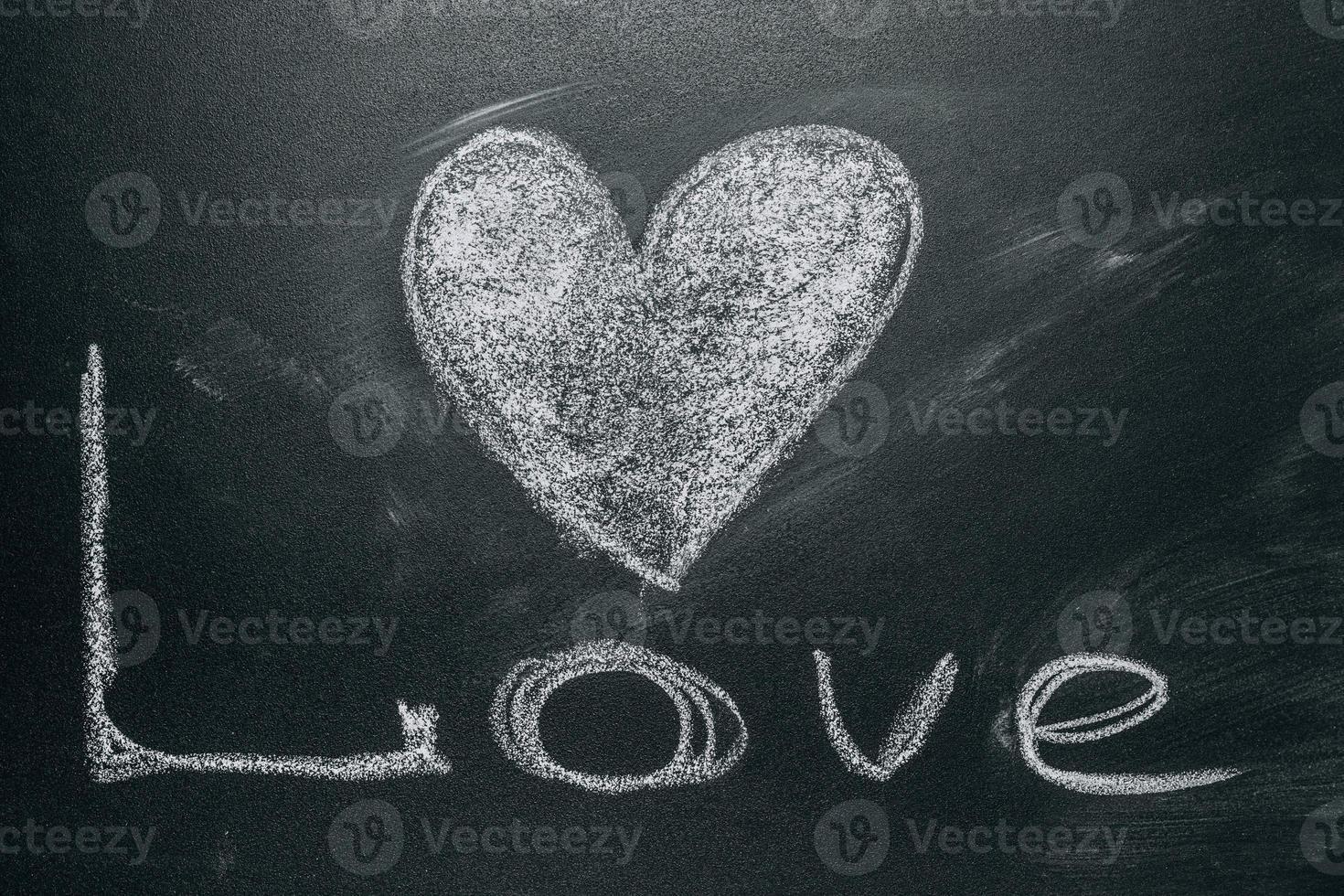 Liebesherz, das auf einer Schultafel zeichnet foto