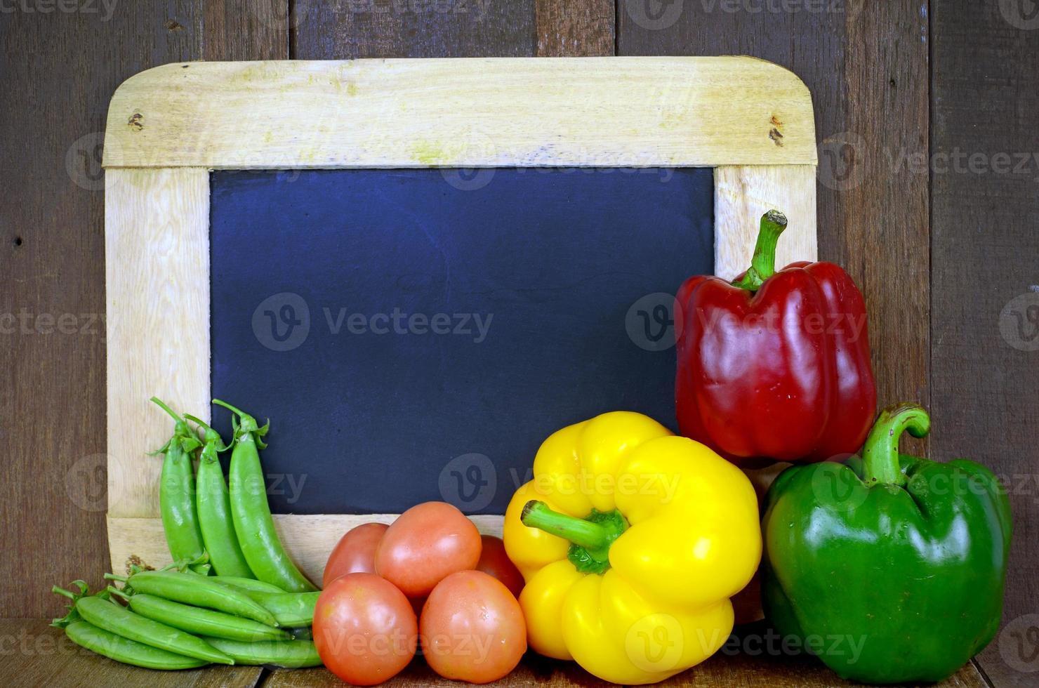 buntes asiatisches Gemüse mit leerer Tafel auf hölzernem Hintergrund foto