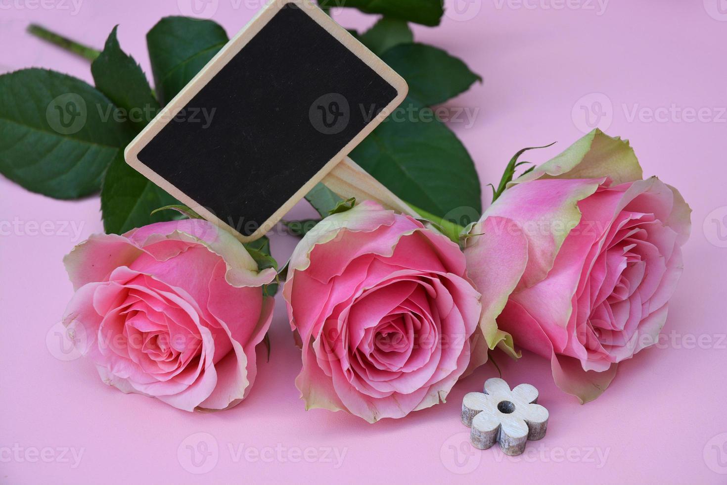 rosa Hintergrund und Rosen, mit leerem schwarzen Kreidetafeletikett foto